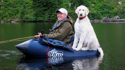 Kent Lufkin in his float tube ... with his big white dog!.