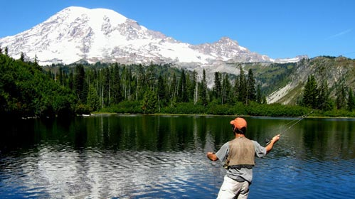 Angler flyfishing with a blue lake and Mt Rainier looming over the scene.