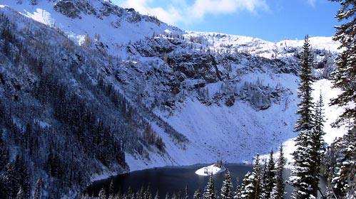 Deep blue lake surround by steep hills covered with fresh snow.